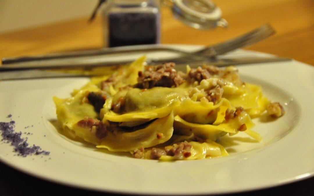 Ravioloni al radicchio con salsa alla salsiccia, crema di latte, granella di nocciole tostate e sale al crauto rosso dello chef Enrico Fiorentini.