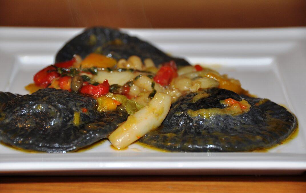 Ravioloni neri con gamberi e triglie su salsa di seppie e peperoni